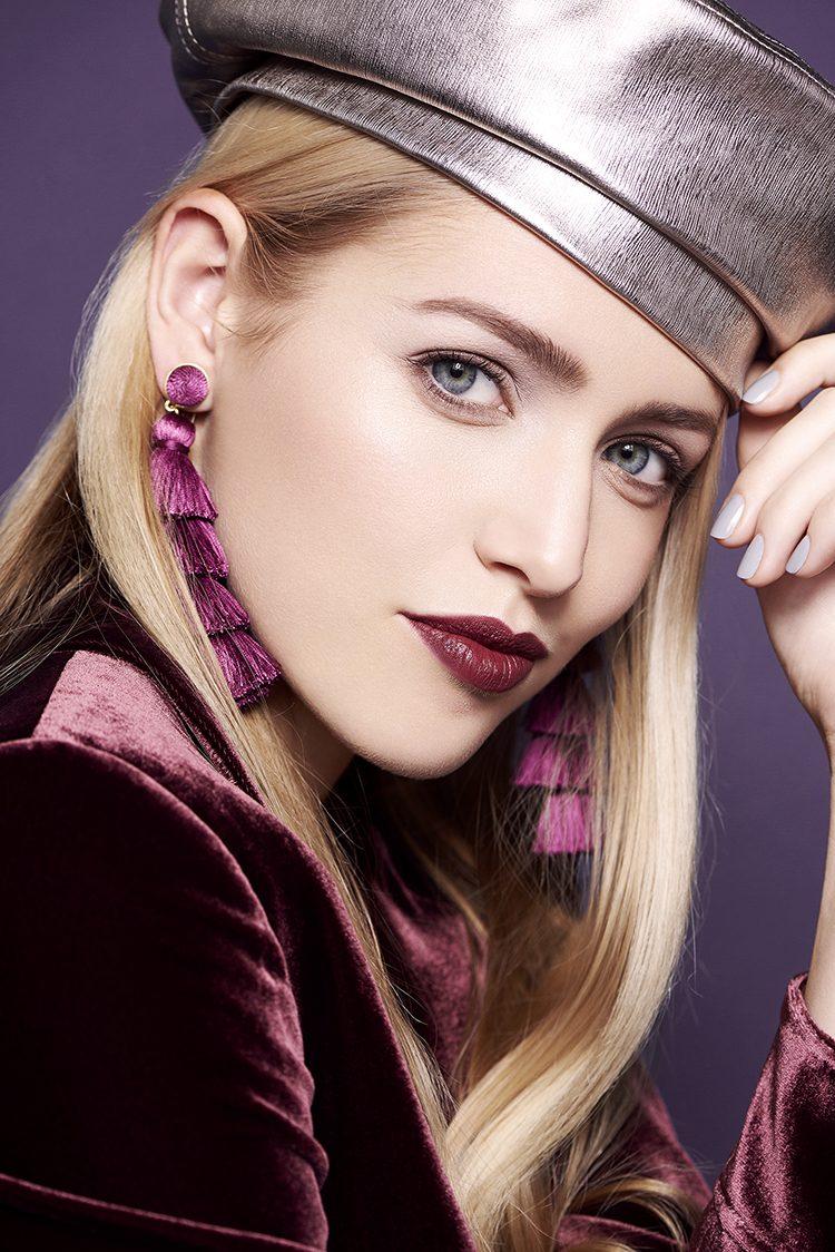 Model wearing a dark berry lipstick and velvet jacket